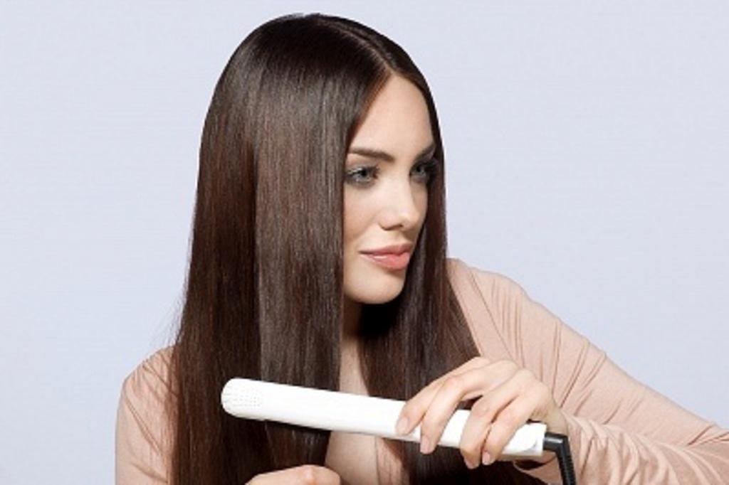Девушка шатенка выпрямляет волосы утюжком