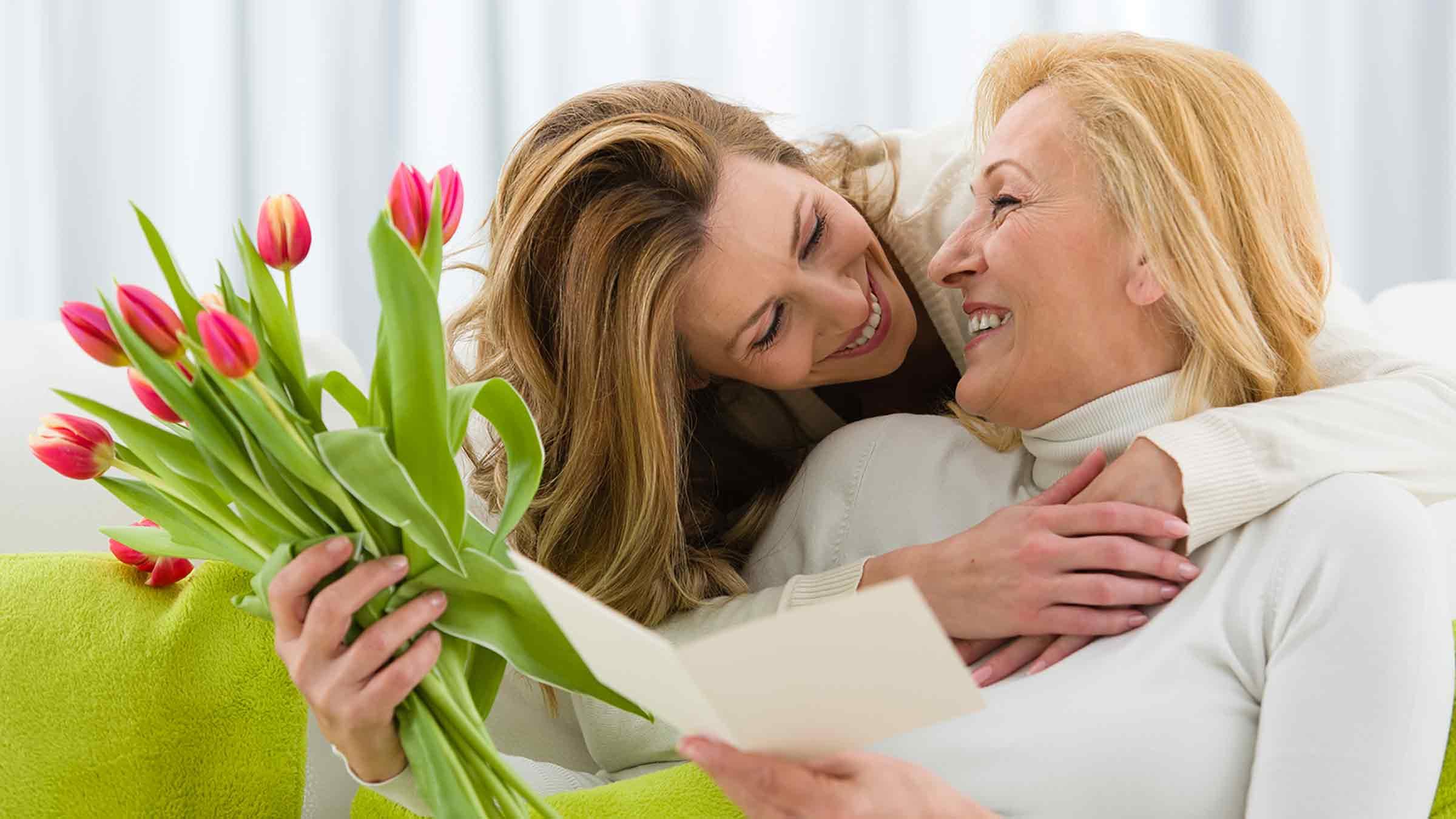 Девушка дарит цветы (тюльпаны) женщина
