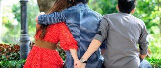 Девушку обнимает парень, а она держит за руку другого