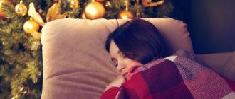 Девушка спит около елки на новый год