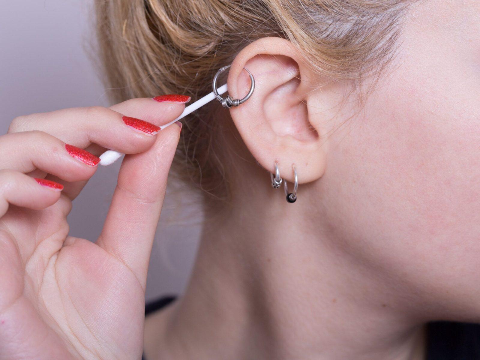 Девушка обрабатывает дырочку в ухе после прокола