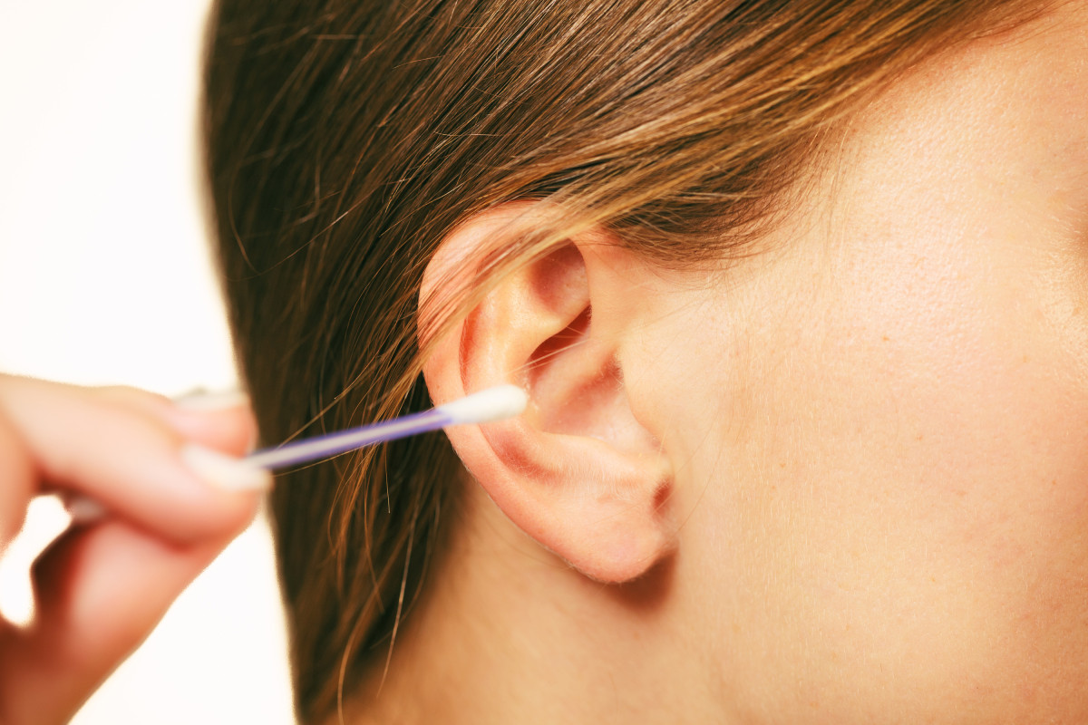 Девушка чистит ухо ватной палочкой