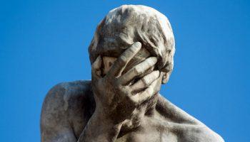 Статуя закрывает рукой лицо
