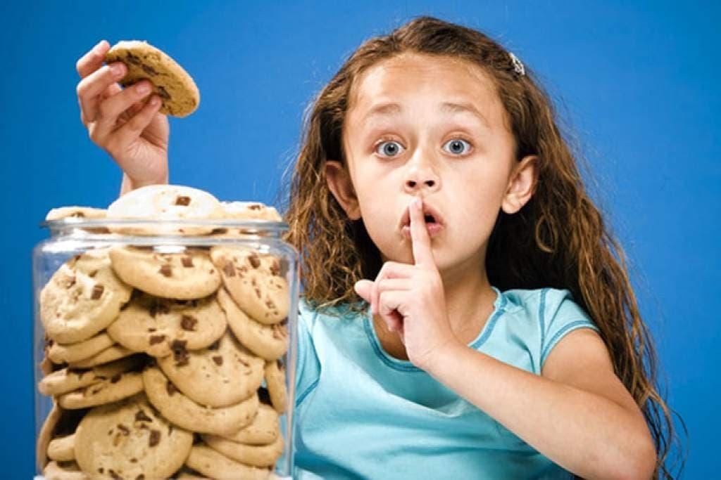 Девочка ест украдкой печенье
