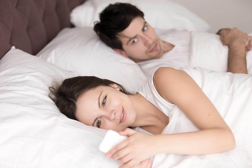 Жена в постели читает сообщение тайком от мужа
